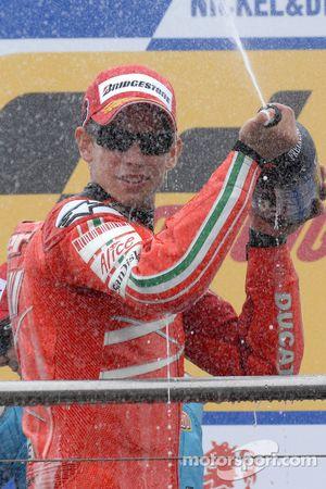 Podio: Ganador de la carrera Casey Stoner celebra con champagne