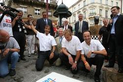 Les vainqueurs des 24 Heures du Mans 2006 Marco Werner, Frank Biela et Emanuele Pirro s'apprêtent à dévoiler la plaque d'égout traditionnels des gagnants dans le centre-ville du Mans
