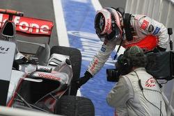 Победитель гонки Фернандо Алонсо указывает на то место, где его машины коснулся Фелипе Масса