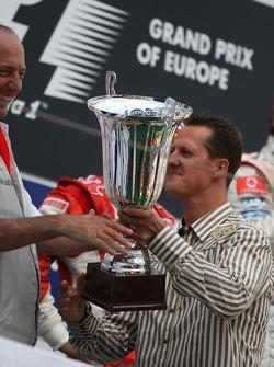 Michael Schumacher hands Ron Dennis the constructor trophy