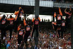 Race winner Tony Stewart and his crew climb the fence