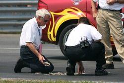 Officiels NASCAR Busch Series inspectant la piste à l'épingle après que l'asphalte ait commencé à se