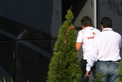 Fernando Alonso y su manager Luis García Abad entran en el autobús de Bernie Ecclestone