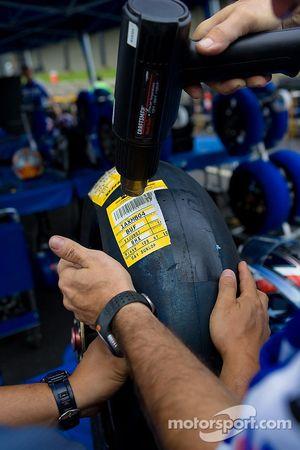 Membres d'équipage Suzuki retirent les étiquettes du nouveau pneu Dunlop