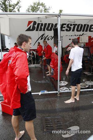 Membres de l'équipe Bridgestone essaient de faire sécher leur paddock