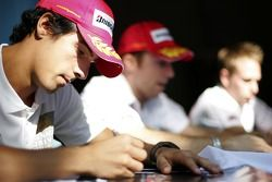 Lucas di Grassi, Jason Tahinci and Adam Carroll sign autographs for the fans