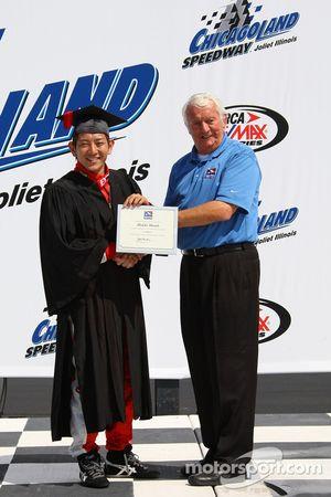 Hideki Mutoh reçoit un certificat de Roger Bailey lors de son déplacement dans la série IndyCar