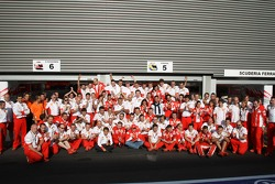 Race winner Kimi Raikkonen celebrates with Felipe Massa and Ferrari team members