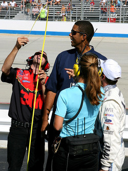 Greg Biffle looks on as a member of his crew checks to see if ESPN analyst Brad Daugherty measures up along pit road