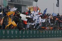 Membres de l'équipe et pilotes heureux sur le mur des stands lorsque les voitures franchissent la li
