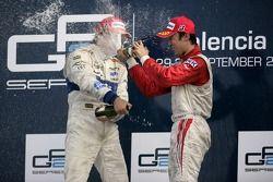 Vitaly Petrov celebrates victory on the podium with Kazuki Nakajima