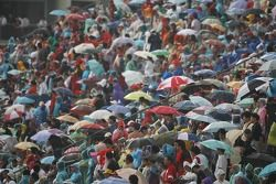 Fans with umbrellas in the rain