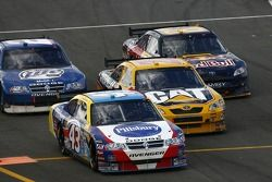 Bobby Labonte leads a group of cars on pit road