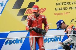 Podium: champagne for Casey Stoner and Dani Pedrosa