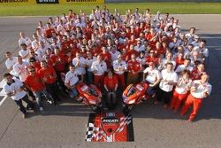 Групповое фото Ducati Marlboro: Кейси Стоунер и Лорис Капиросси позируют с членами команды Ducati Ma