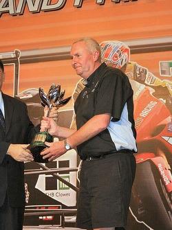 John Booth collects Kodai Tsukakoshi's trophy