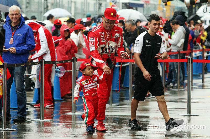 A young Ferrari fan and his father welcomed into the McLaren pit garage