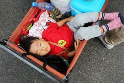 Un joven fan duerme en un carreola