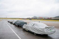 Autos con la cubierta para la lluvia en el pit lane