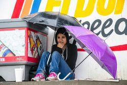 Una aficionada se cubre de la lluvia en las tribunas