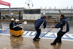 Williams mechanics practice their boating skills in the wet pit lane