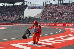 Un commissaire enlève la carcasse du pneu de Sebastian Vettel, Ferrari