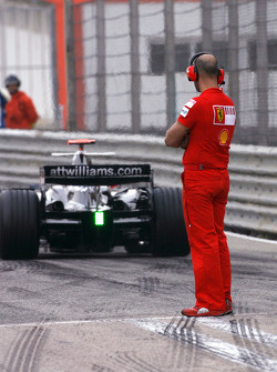 Scuderia Ferrari mechanic looks the new Williams FW30