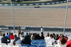 Фанаты на главной трибуне и проезжающий мимо Льюис Хэмилтон, McLaren Mercedes