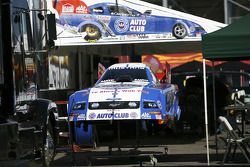 Robert Hight's funny car body sits on stand under pit overhang