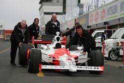 Penske Racing crew members push the car to pitlane