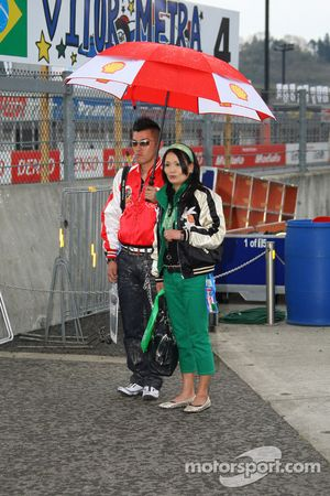Fans protect themselves from the rain