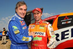 Rally winner Carlos Sainz celebrates with runner-up Stéphane Peterhansel