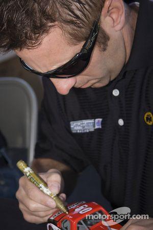 Greg Biffle signs a couple autographs at a go-kart event