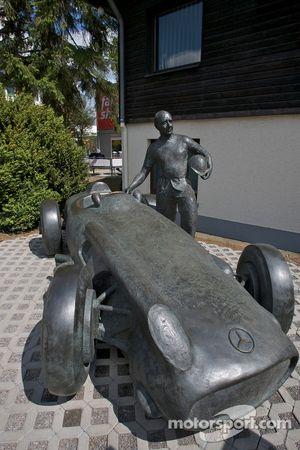 Una estatua de bronce de Juan Manuel Fangio y su Mercedes-Benz W196 en la entrada de la pista