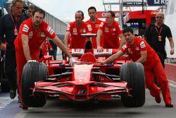 Mecánicos de Scuderia Ferrari, empujan el F2008 en pitlane mientras el experto técnico, Giorgio Piol