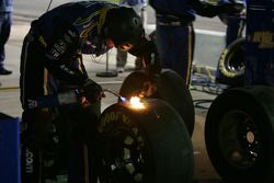 A crew member burns off marbles on the tires