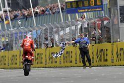 Race winner Casey Stoner takes the checkered flag
