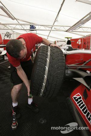 A ART Grand Prix mechanic fits a tyre on Romain Grosjean car