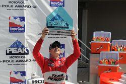 Ryan Briscoe raises his pole trophy triumphantly
