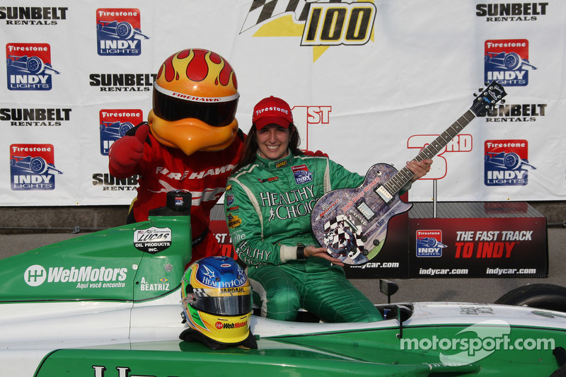 Victory lane: race winner Ana Beatriz celebrates with her winning guitar