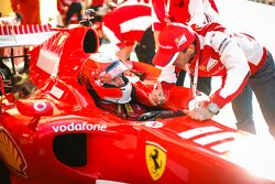 Un pilote Ferrari F1 Clienti en discussion avec un technicien