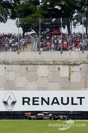 Romain Grosjean, Lotus F1 E23 passe devant un panneau publicitaire Renault