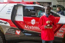 Samba, un enfant sénégalais sauvé par Mécénat Chirurgie Cardiaque, avec le Peugeot 2008 DKR15+ de Romain Dumas et François Borsotto