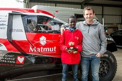 Romain Dumas and Samba, a Senegalese boy who was saved thanks to Mécénat Chirurgie Cardiaque, with the Peugeot 2008 DKR15+