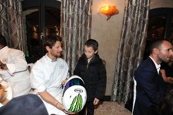 Romain Grosjean mette un casco a un bambino