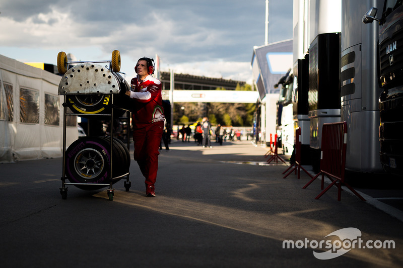Ferrari mechanic with Pirelli tyres in the paddock