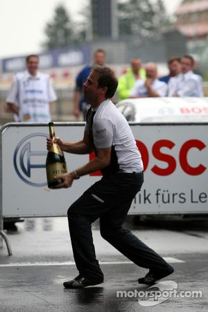 Gerhard Ungar, Chief Designer AMG cathing the bottle of champagne being trown down from the podium