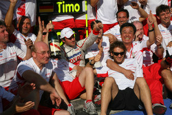 Timo Glock celebrates with Jarno Trulli and Toyota F1 team
