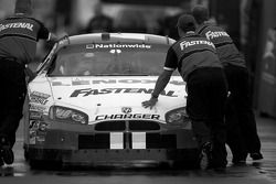 Fastenal Dodge crew members push the #40 car back to the garage after tech inspection