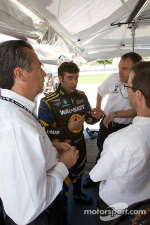 Alex Tagliani discute avec son équipe sous le regard d'Éric Bachelart
